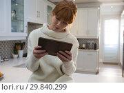 Купить «Woman using digital tablet in kitchen», фото № 29840299, снято 3 августа 2017 г. (c) Wavebreak Media / Фотобанк Лори