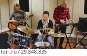 Купить «Rehearsal of music group. Rock band with emotional female drummer playing in recording studio», видеоролик № 29848835, снято 13 ноября 2018 г. (c) Яков Филимонов / Фотобанк Лори