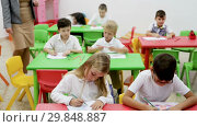 Купить «Group of diligent schoolkids drawing with cheerful female teacher at classroom», видеоролик № 29848887, снято 18 декабря 2018 г. (c) Яков Филимонов / Фотобанк Лори