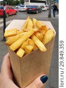 Купить «Картофель фри в руке. Уличная еда.», фото № 29849359, снято 2 июля 2018 г. (c) Милана Харитонова / Фотобанк Лори