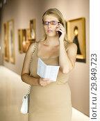 Купить «Female visitor with information booklet», фото № 29849723, снято 22 сентября 2018 г. (c) Яков Филимонов / Фотобанк Лори