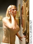 Купить «Woman trying to see picture», фото № 29849727, снято 22 сентября 2018 г. (c) Яков Филимонов / Фотобанк Лори