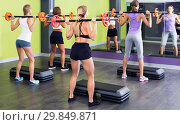 Купить «Portrait of sporty women exercising with barbell in fitness club», фото № 29849871, снято 26 июля 2017 г. (c) Яков Филимонов / Фотобанк Лори