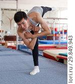 Купить «Positive man acrobat exercising gymnastic action at sport gym», фото № 29849943, снято 18 июля 2018 г. (c) Яков Филимонов / Фотобанк Лори