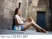 Купить «Young woman sitting near old stone wall», фото № 29851887, снято 15 августа 2017 г. (c) Яков Филимонов / Фотобанк Лори