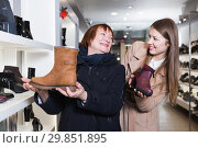 Купить «Young smiling female and her mother are choosing modern ankle boots», фото № 29851895, снято 13 декабря 2017 г. (c) Яков Филимонов / Фотобанк Лори