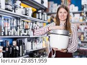 Polite salesgirl suggesting slow cooker in store. Стоковое фото, фотограф Яков Филимонов / Фотобанк Лори