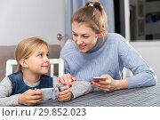 Купить «Happy mother and daughter with smartphone at home», фото № 29852023, снято 22 января 2019 г. (c) Яков Филимонов / Фотобанк Лори