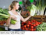 friendly young female customer holding fresh celery and leek. Стоковое фото, фотограф Яков Филимонов / Фотобанк Лори