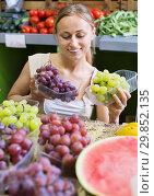 Woman customer buying sweet ripe grapes on marketplace. Стоковое фото, фотограф Яков Филимонов / Фотобанк Лори