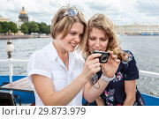 Купить «Happy and smiling young women looking on camera screen at pictures», фото № 29873979, снято 14 июля 2012 г. (c) Кекяляйнен Андрей / Фотобанк Лори