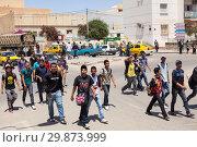Толпа агрессивных подростков идет по середине дороги в провинциальном городе Туниса, Африка (2012 год). Редакционное фото, фотограф Кекяляйнен Андрей / Фотобанк Лори