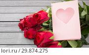 Купить «close up of red roses and greeting card with heart», фото № 29874275, снято 8 февраля 2018 г. (c) Syda Productions / Фотобанк Лори