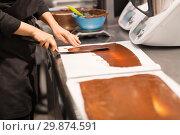 Купить «confectioner makes chocolate dessert at sweet-shop», фото № 29874591, снято 4 декабря 2018 г. (c) Syda Productions / Фотобанк Лори