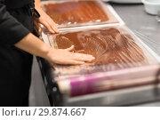 Купить «confectioner makes chocolate dessert at sweet-shop», фото № 29874667, снято 4 декабря 2018 г. (c) Syda Productions / Фотобанк Лори