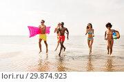 Купить «friends run with beach ball and swimming mattress», фото № 29874923, снято 29 июля 2018 г. (c) Syda Productions / Фотобанк Лори