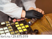 Купить «worker packing candies at confectionery shop», фото № 29875019, снято 4 декабря 2018 г. (c) Syda Productions / Фотобанк Лори
