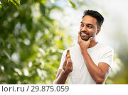 Купить «smiling indian man applying grooming oil to beard», фото № 29875059, снято 27 октября 2018 г. (c) Syda Productions / Фотобанк Лори