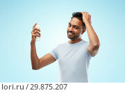 Купить «smiling indian man applying hair spray over blue», фото № 29875207, снято 27 октября 2018 г. (c) Syda Productions / Фотобанк Лори