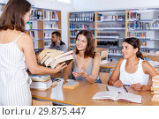 Купить «Two young female students working in university library, taking stack of books brought by woman librarian», фото № 29875447, снято 26 июля 2018 г. (c) Яков Филимонов / Фотобанк Лори