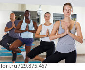 Купить «Group of sporty adult women and men practicing yoga asana», фото № 29875467, снято 30 июля 2018 г. (c) Яков Филимонов / Фотобанк Лори