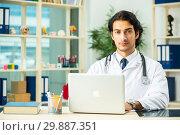 Купить «Young handsome doctor in telemedicine concept», фото № 29887351, снято 12 ноября 2018 г. (c) Elnur / Фотобанк Лори