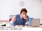 Купить «Young handsome employee working in the office», фото № 29889251, снято 5 октября 2018 г. (c) Elnur / Фотобанк Лори
