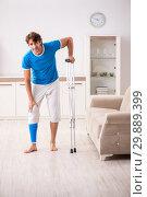 Купить «Leg injured young man with crutches at home», фото № 29889399, снято 19 сентября 2018 г. (c) Elnur / Фотобанк Лори