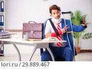Купить «Injured employee working in the office», фото № 29889467, снято 20 сентября 2018 г. (c) Elnur / Фотобанк Лори
