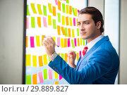Купить «Young handsome employee with many conflicting priorities», фото № 29889827, снято 15 августа 2018 г. (c) Elnur / Фотобанк Лори