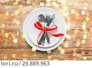 Купить «cutlery tied with red ribbon on set of plates», фото № 29889963, снято 9 февраля 2018 г. (c) Syda Productions / Фотобанк Лори