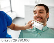 Купить «dentist choosing tooth color for patient at clinic», фото № 29890003, снято 22 апреля 2018 г. (c) Syda Productions / Фотобанк Лори