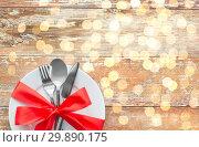 Купить «cutlery tied with red ribbon on set of plates», фото № 29890175, снято 9 февраля 2018 г. (c) Syda Productions / Фотобанк Лори