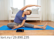 Купить «woman with tablet computer doing yoga at home», фото № 29890235, снято 13 ноября 2015 г. (c) Syda Productions / Фотобанк Лори