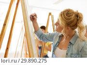 Купить «woman with easel drawing at art school studio», фото № 29890275, снято 26 мая 2017 г. (c) Syda Productions / Фотобанк Лори