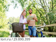 couple with map and bicycles at country in summer. Стоковое фото, фотограф Syda Productions / Фотобанк Лори