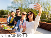 Купить «happy friends taking selfie at rooftop party», фото № 29890419, снято 2 сентября 2018 г. (c) Syda Productions / Фотобанк Лори