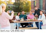 Купить «happy friends photographing at rooftop party», фото № 29890427, снято 2 сентября 2018 г. (c) Syda Productions / Фотобанк Лори