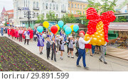 Russia, Samara, May 2018: Graduates of schools during the festive procession carry in their hands an imitation of a school bell from balloons. Редакционное фото, фотограф Акиньшин Владимир / Фотобанк Лори