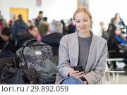 Купить «Cheerful female traveler smiling, looking at camera while reading on her cell phone while waiting to board a plane at departure gates at airport terminal.», фото № 29892059, снято 10 января 2019 г. (c) Matej Kastelic / Фотобанк Лори