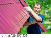 Купить «Portrait of repairman in the background of the roof of a private house, is engaged in repair», фото № 29897535, снято 23 июня 2016 г. (c) Константин Лабунский / Фотобанк Лори