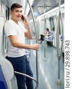 Купить «Man traveling on subway and talking on smartphone», фото № 29898743, снято 24 августа 2018 г. (c) Яков Филимонов / Фотобанк Лори