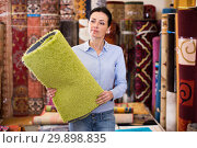 Купить «Cheerful woman customer shopping carpet in store», фото № 29898835, снято 22 ноября 2017 г. (c) Яков Филимонов / Фотобанк Лори