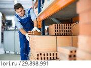 Купить «man is calculating bricks before selling», фото № 29898991, снято 26 июля 2017 г. (c) Яков Филимонов / Фотобанк Лори
