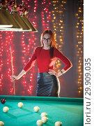 Купить «A ginger woman in black skirt standing in billiard club holding a cue», фото № 29909035, снято 5 февраля 2019 г. (c) Константин Шишкин / Фотобанк Лори