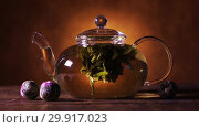 Купить «Green Chinese Tea Flower Bud Blooming in Glass Teapot on a beige background», видеоролик № 29917023, снято 10 февраля 2019 г. (c) Алексей Кузнецов / Фотобанк Лори
