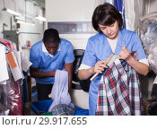 Купить «Female laundry worker during daily work», фото № 29917655, снято 15 января 2019 г. (c) Яков Филимонов / Фотобанк Лори