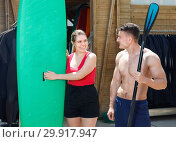 Купить «Young couple planning to surf, choosing boards and surfing suits in beach club», фото № 29917947, снято 30 апреля 2018 г. (c) Яков Филимонов / Фотобанк Лори