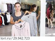 Купить «Woman holding and showing blouse on hanger», фото № 29942723, снято 10 октября 2018 г. (c) Яков Филимонов / Фотобанк Лори
