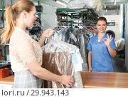 Купить «Worker of dry cleaner returning clean clothes», фото № 29943143, снято 9 мая 2018 г. (c) Яков Филимонов / Фотобанк Лори